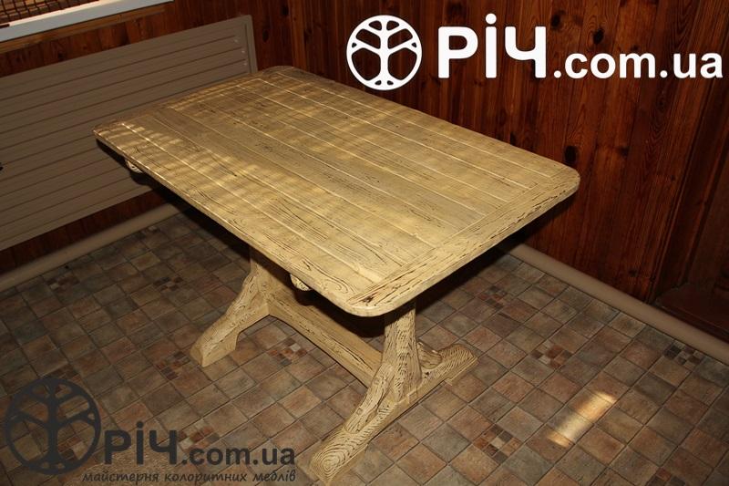Дерев'яний обідній стіл під старовину. В інтер'єрі кухні.